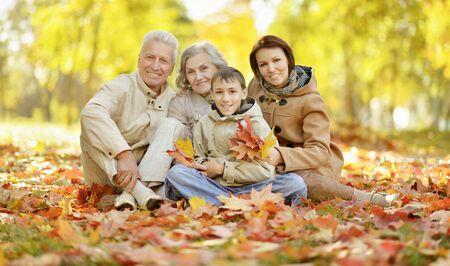 Linda familia feliz relajante en el bosque de otoño