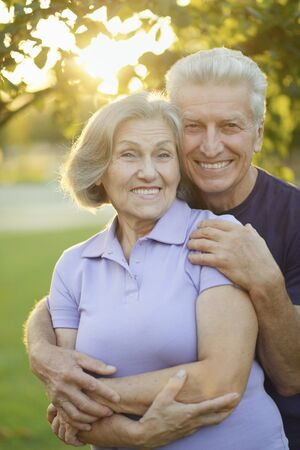 Portrait of happy senior couple posing in park
