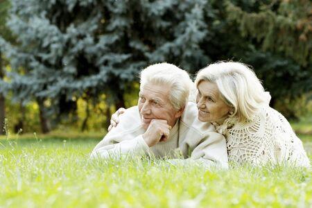 Portrait of beautiful senior couple lying on grass