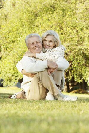 Portrait of beautiful senior couple sitting on grass
