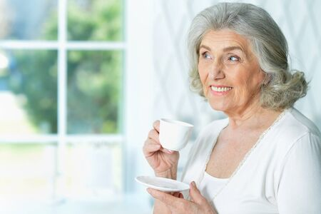 Portrait of beautiful smiling senior woman drinking tea