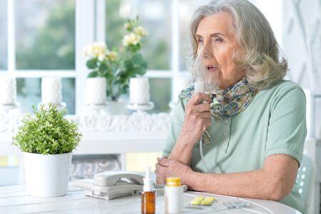 Sick senior woman sitting at kitchen with inhaler