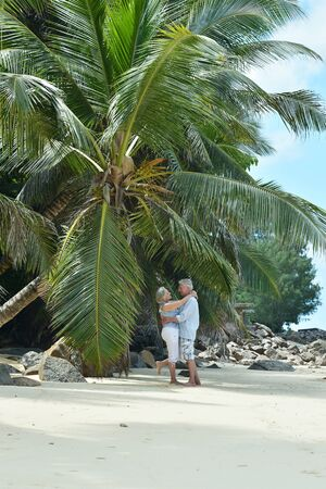 Portrait of happy elderly couple hugging on tropical beach