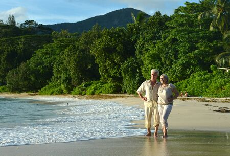 Happy elderly couple rest at tropical beach