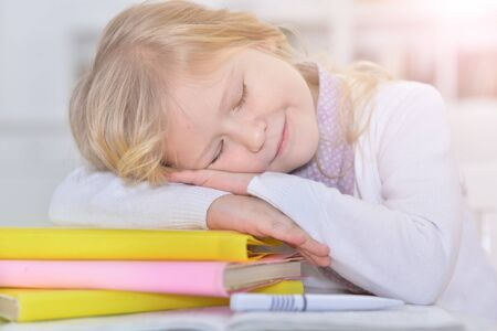Cute schoolgirl sleeping on table after doing homework at home