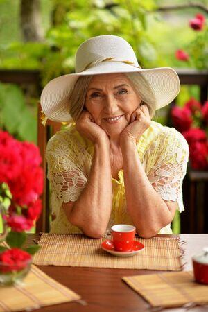 Portrait of happy aged woman drinking coffee Reklamní fotografie