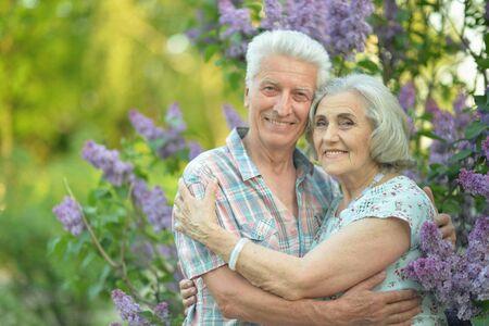 Senior couple hugging on a lilac background in the park Reklamní fotografie