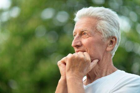 Close up portrait of smiling senior man in park