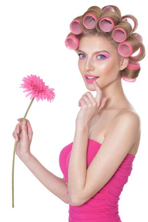 Portrait of beautiful woman with hair curlers holding flower