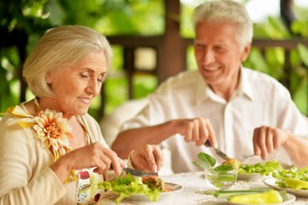 Portrait of happy senior couple having diner and posing on the veranda Reklamní fotografie