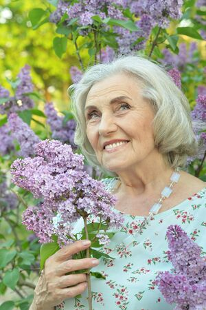 Close up portrait of happy senior beautiful woman with lilacs