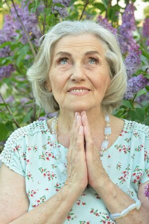 Close up portrait of senior beautiful smiling woman praying