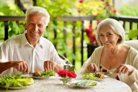 Close up portrait of happy senior couple having diner