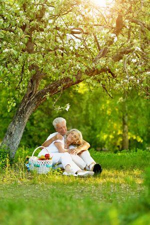 Elderly couple having a picnic in the summer garden Reklamní fotografie