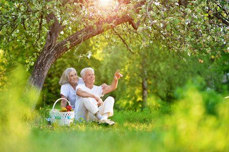 Loving elderly couple having a picnic in the summer garden
