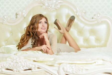 Beautiful young woman posing on bed at home Reklamní fotografie