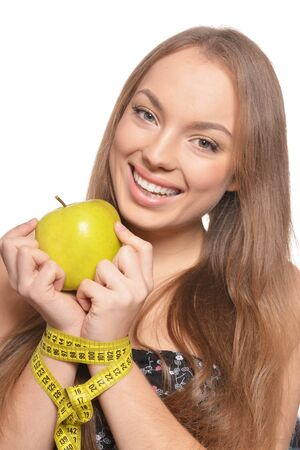 Portrait of beautiful young woman with green apple and measuring tape