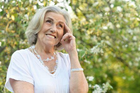 Senior smilling beautiful woman posing in spring park