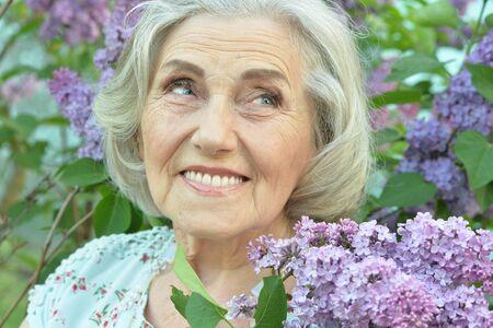 Close up portrait of happy senior beautiful woman with lilacs Reklamní fotografie - 140988268