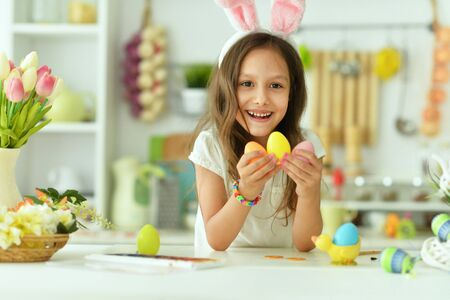 Beautiful girl in bunny ears painting eggs for Easter holiday
