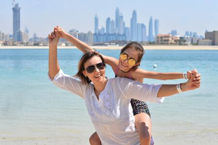 Happy mother with daughter posing on beach