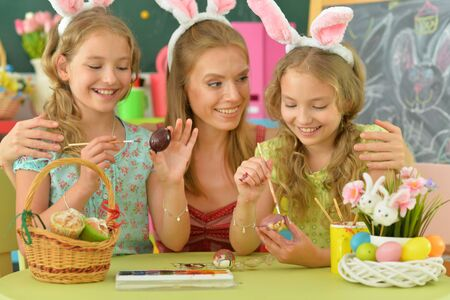 Mother with daughters wearing rabbit ears decorating Easter eggs