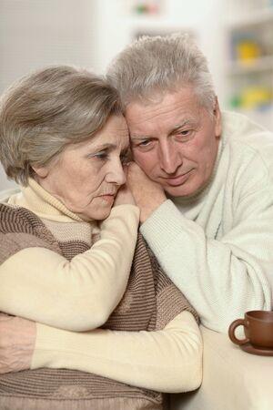 Portrait of sad senior couple posing at home