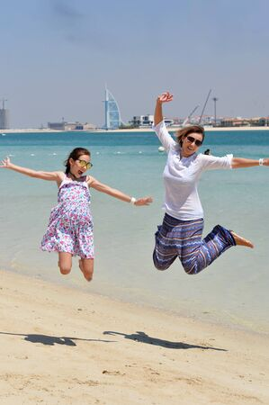 Heureuse mère avec sa fille sautant sur la plage
