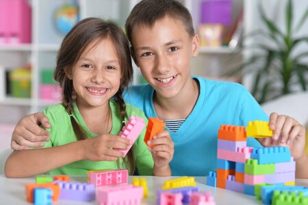 Portrait of brother and sister playing with colorful plastic blocks Foto de archivo