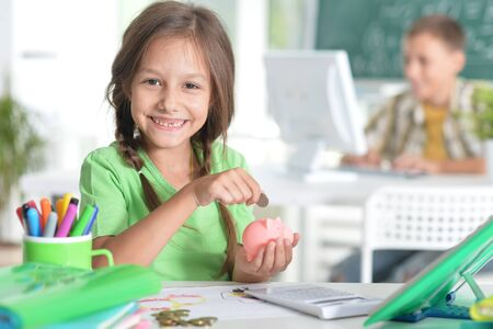Portrait of cute teen girl putting coins in piggy bank