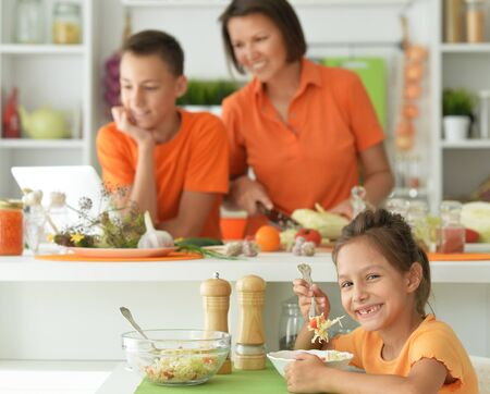 Portrait of cute girl eating delicious fresh salad in kitchen