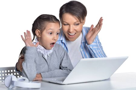 Portrait of emotional mother and daughter using laptop