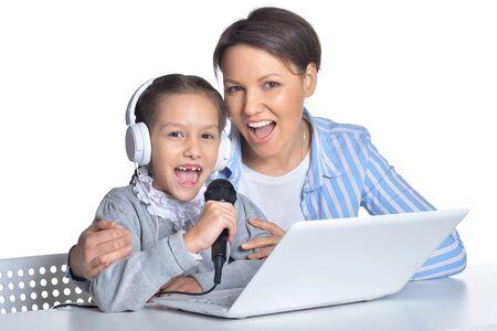 Portrait of mother and daughter singing karaoke Imagens