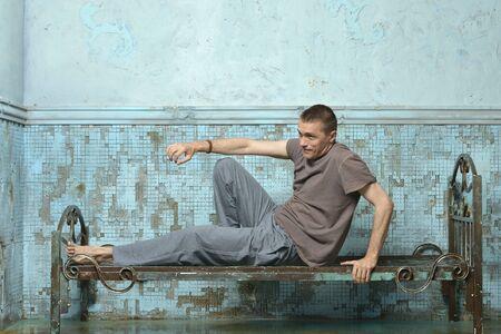 Man on the metal rusty bed in prison 免版税图像