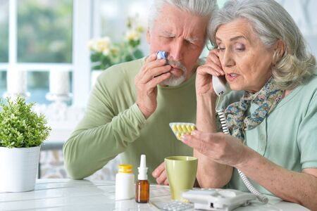 Close up portrait of ill senior couple with pills at home Stock Photo