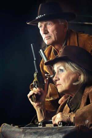 Portrait of gunslingers in western garment on black