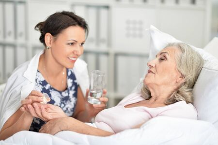 Senior woman in hospital with caring daughter