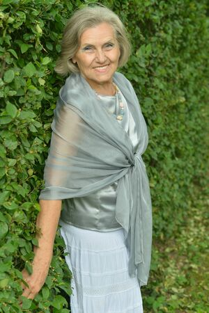 Portrait of senior smiling woman in park