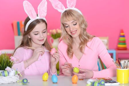 Portrait of mother and daughter colouring eggs 스톡 콘텐츠