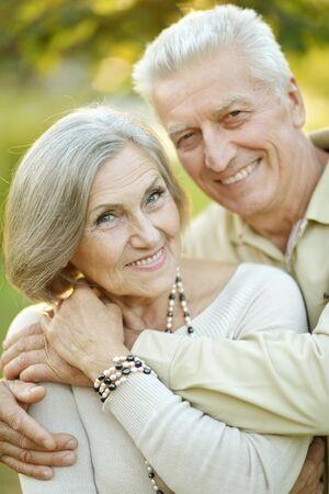 Smiling senior couple embracing in autumn park
