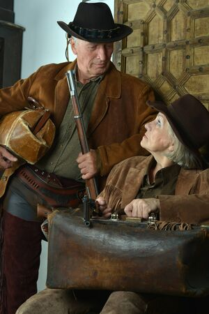 Happy gunslingers in western garment on black Stockfoto