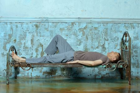 Portrait of man on the metal rusty bed in prison