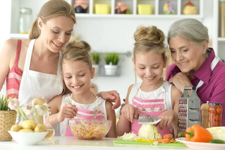 Cute girls with mother preparing delicious fresh salad in kitchen