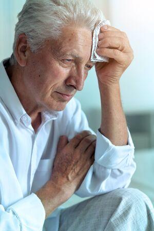 Portrait of sad sick senior man with headache