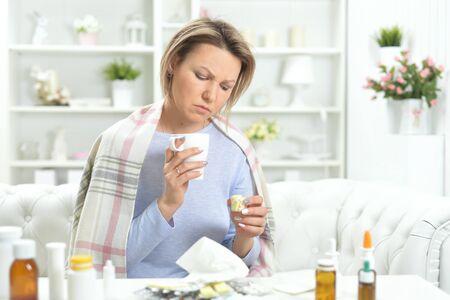 Portrait of beautiful young woman taking pills