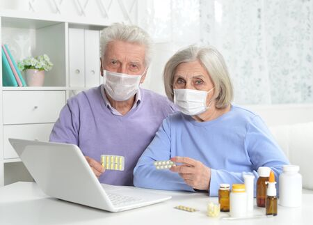 Ill senior couple with facial masks using laptop