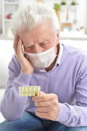 Portrait of sad sick senior man with facial mask holding pills