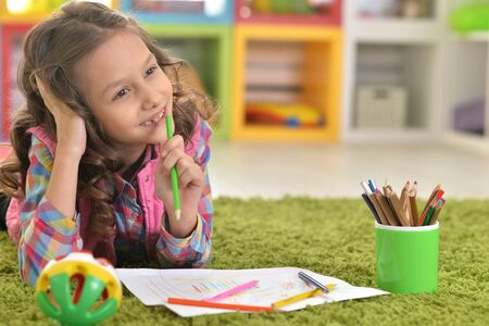 Portrait of beautiful little girl drawing at her room at home