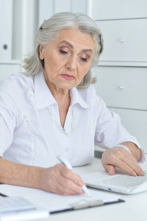 Portrait of senior female doctor working at her cabinet