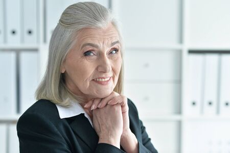 Close up portrait of emotional old businesswoman in office Фото со стока